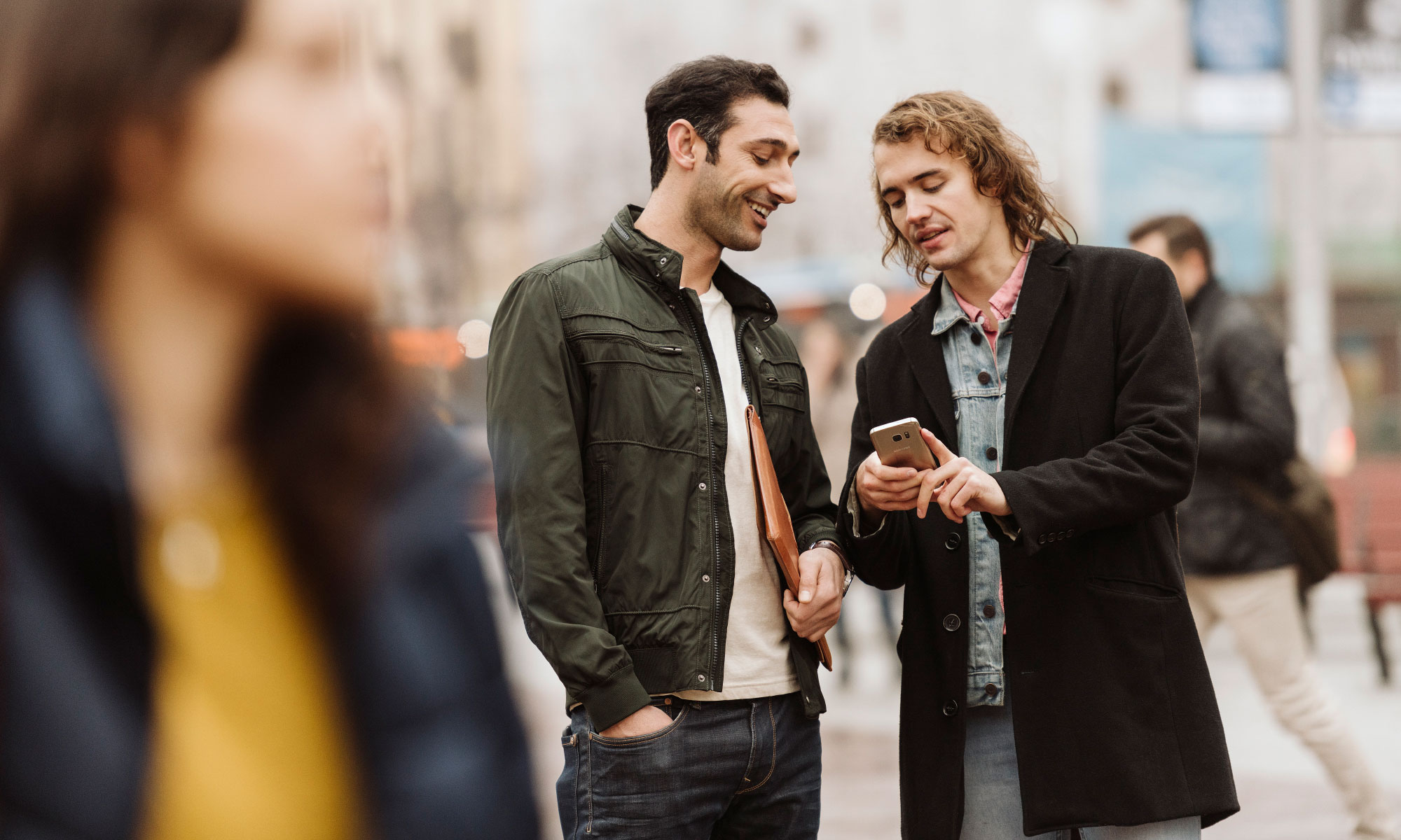 A man showing his friend something on his mobile.